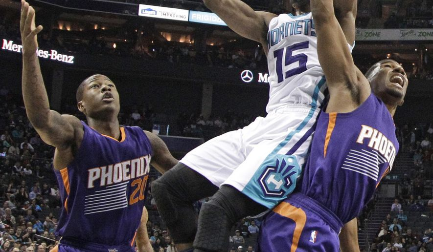 Charlotte Hornets' Kemba Walker (15) is fouled as he drives between Phoenix Suns' Archie Goodwin (20) and Ronnie Price during the first half of an NBA basketball game in Charlotte, N.C., Tuesday, March 1, 2016. (AP Photo/Chuck Burton)