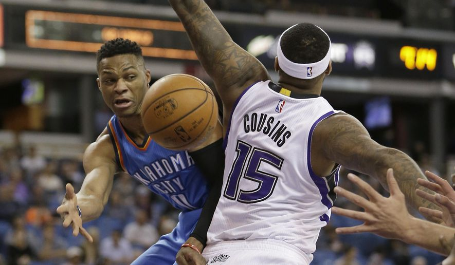 Oklahoma City Thunder guard Russell Westbrook, left, slips the ball past Sacramento Kings center DeMarcus Cousins during the first quarter of an NBA basketball game Monday, Feb. 29, 2016, in Sacramento, Calif.(AP Photo/Rich Pedroncelli)