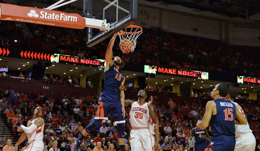 Virginia's Anthony Gill dunks as Clemson's Landry Nnoko (35) watches during the first half of an NCAA college basketball game Tuesday, March 1, 2016, in Greenville, S.C. (AP Photo/Richard Shiro)