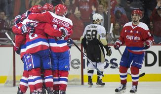 Washington Capitals defenseman Matt Niskanen, left, is congratulated by teammates after scoring against the Pittsburgh Penguins during the third period of an NHL hockey game, on Tuesday, March 1, 2016, in Washington. The Capitals won 3-2. (AP Photo/Evan Vucci)