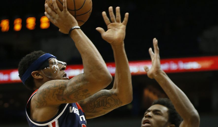 Washington Wizards guard Bradley Beal (3) shoots the ball against Minnesota Timberwolves forward Andrew Wiggins (22) in the second half of an NBA basketball game Wednesday, March 2, 2016 in Minneapolis. The Wizards won 104-98. (AP Photo/Stacy Bengs)
