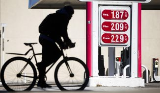 A cyclist passes posted gasoline prices at a filling station, Wednesday, March 2, 2016, in Philadelphia. Gasoline prices are expected to keep rising until summer but remain far cheaper than in recent years, due to the worldwide glut of oil. (AP Photo/Matt Rourke)