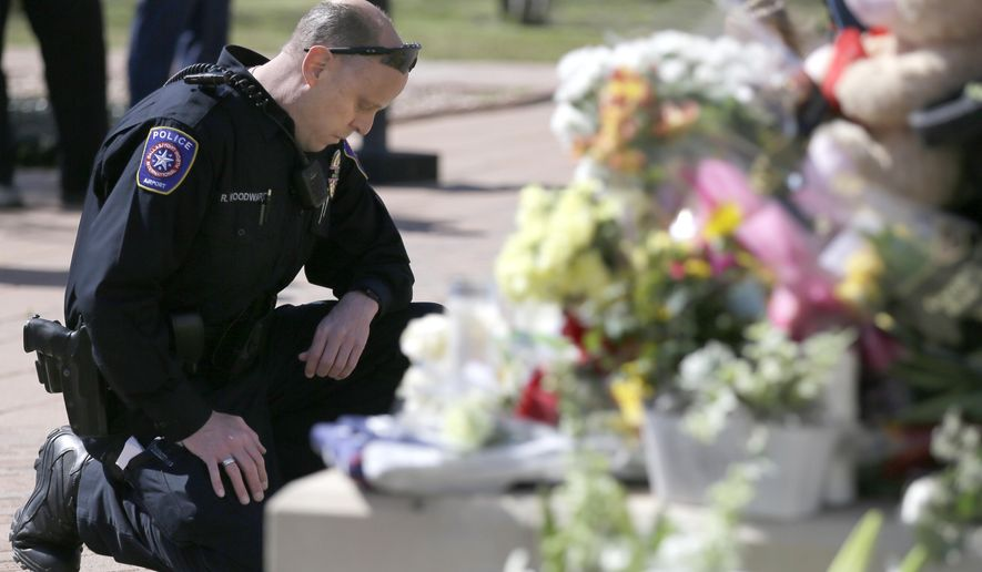 DFW Airport Police officer Robert Woodward kneels in front of a makeshift memorial for a slain officer at the Euless Police Department  Wednesday, March 2, 2016, in  Euless, Texas. Officer David Hofer died after he was shot in a Tuesday afternoon gunfight with an armed suspect in a park near a Dallas-area school, police said. Hofer, who previously worked for the New York Police Department, died during surgery. The suspect was also killed. (AP Photo/LM Otero)