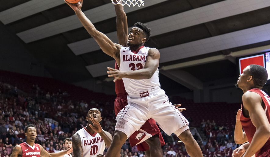 Alabama guard Retin Obasohan (32) gets inside past Arkansas forward Moses Kingsley during an NCAA college basketball game Wednesday, March 2, 2016, in Tuscaloosa, Ala. (Vasha Hunt/AL.com via AP)