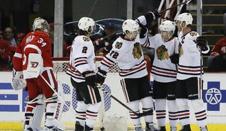 Chicago Blackhawks' Artemi Panarin (72), of Russia, celebrates with teammates Duncan Keith (2), Patrick Kane, second from right, and and Jonathan Toews, right, after scoring on Detroit Red Wings goalie Petr Mrazek (34) during the second period of an NHL hockey game Wednesday, March 2, 2016, in Detroit. (AP Photo/Duane Burleson)