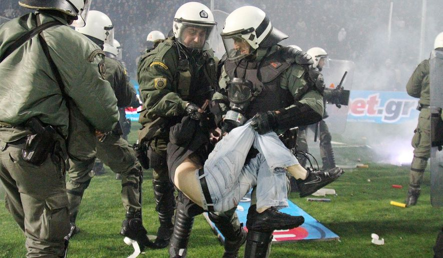 Riot police detain a fan during a Greek Cup semifinal match between PAOK and champion Olympiakos at the Toumba stadium in the northern Greek city of Thessaloniki, Wednesday, March 2, 2016. The match has been stopped in the final minute after home fans threw flares onto the pitch and ran onto the field to clash with riot police. The first-leg match was stopped in the 90 minute as Olympiakos led 2-1. (InTime Sports via AP)  GREECE OUT