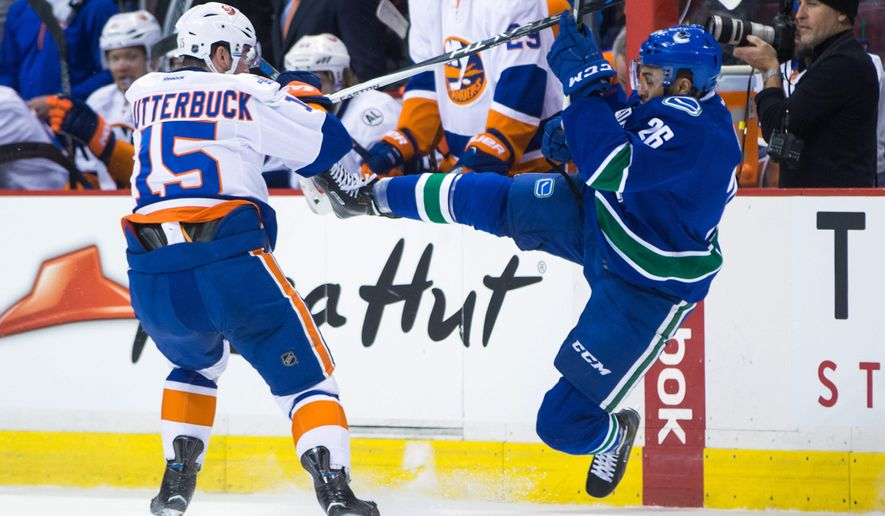 New York Islanders' Cal Clutterbuck, left, checks Vancouver Canucks' Emerson Etem during the first period of an NHL hockey game Tuesday, March 1, 2016, in Vancouver, British Columbia. (Darryl Dyck/The Canadian Press via AP)