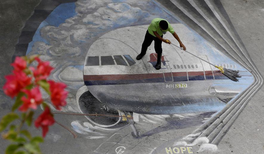 "FILE - In this April 8, 2014, file photo a school utility worker mops a mural depicting the missing Malaysia Airlines Flight 370 at the Benigno ""Ninoy"" Aquino High School campus at Makati city east of Manila, Philippines. A U.S. official says debris washed up over the weekend in Mozambique has been tentatively identified by experts close to the investigation as a part from the tail of the same type of aircraft as the missing Malaysia Airlines Flight 370.  (AP Photo/Bullit Marquez, File)"