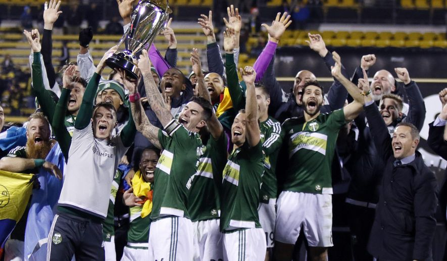 FILE - In this Dec. 6, 2015, file photo, Portland Timbers raise the trophy after defeating the Columbus Crew 2-1 in the MLS Cup championship soccer game in Columbus, Ohio. After celebrating its 20th anniversary a year ago with an appreciation for the ups and downs that got MLS to age 20, the league is now moving into its next stage of continuing growth while competing with other leagues around the world.  (AP Photo/Paul Vernon, File)