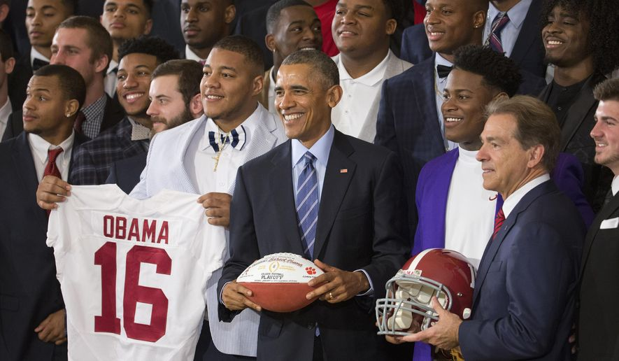 President Barack Obama holds a football for a group portrait as he honors the 2015-2016 College Football Playoff National Champion Alabama Crimson Tide football team, Wednesday, March 2, 2016, during a ceremony in the East Room of the White House in Washington. At right is Alabama Crimson Tide head coach Nick Saban. (AP Photo/Pablo Martinez Monsivais)