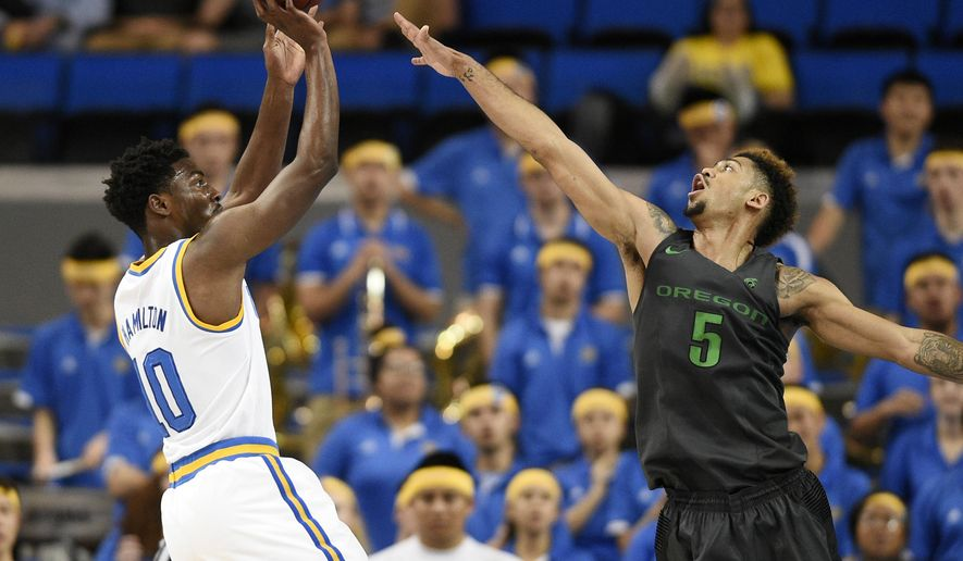 UCLA guard Isaac Hamilton, left, attempts a shot while Oregon guard Tyler Dorsey, right, defends during the first half of an NCAA college basketball game in Los Angeles, Wednesday, March 2, 2016. (AP Photo/Kelvin Kuo)
