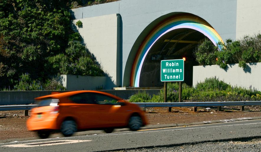 In this photo from Tuesday, March 1, 2016, a sign stands at the northbound entrance to the recently renamed Robin Williams Tunnel in Sausalito, Calif. A tunnel with rainbow arches that connects the Golden Gate Bridge to greater Marin County has officially become the Robin Williams tunnel. The tunnel was unofficially known as the Waldo Tunnel. The California State Senate last year approved a resolution to change the tunnel's name to honor the late actor and comedian. Williams grew up and lived in the Bay Area. (Alan Dep/Marin Independent Journal via AP)