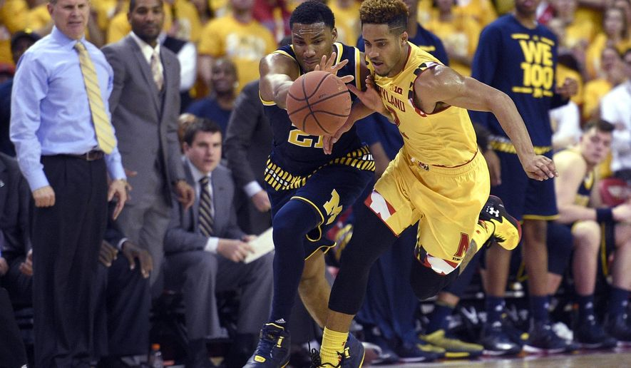 FILE - In this Feb. 21, 2016, file photo, Michigan guard Zak Irvin, left, and Maryland guard Melo Trimble, right, chase the ball during an NCAA college basketball game in College Park, Md. As tournament time draws closer, No. 14 Maryland is playing its worst basketball of the season and looking less and less like a contender for the national championship. (AP Photo/Nick Was, Files)