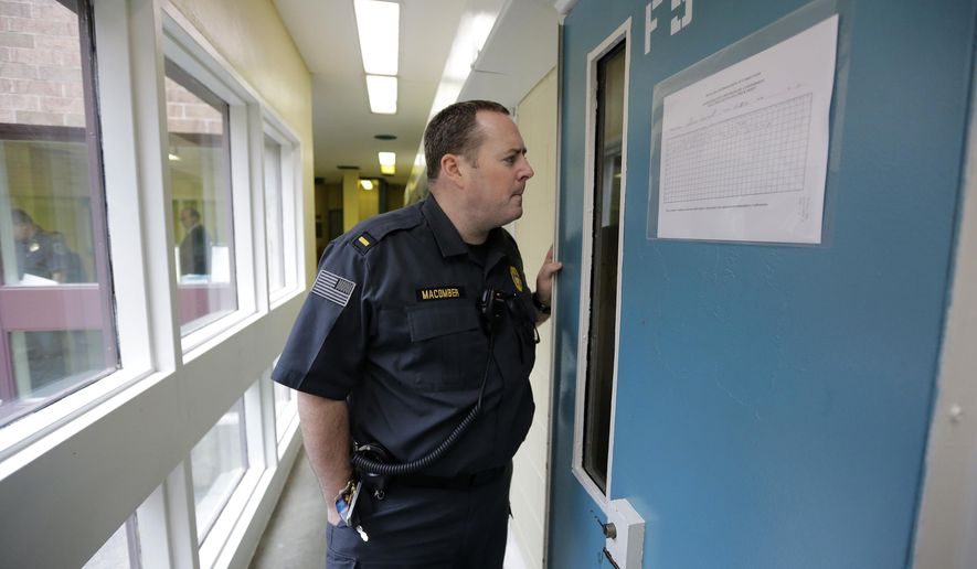 In this Thursday, Feb. 25, 2016 photo, correctional officer Lt. Joshua Macomber speaks with an inmate through a glass window to a door to what prison officials describe as a cell in an administrative segregation area rather than solitary confinement, at the Rhode Island Department of Corrections High Security Center, in Cranston, R.I. A national movement against the solitary confinement of prisoners has moved to Rhode Island, where some lawmakers have proposed limiting the isolation of inmates to no more than 15 days at a time. (AP Photo/Steven Senne)