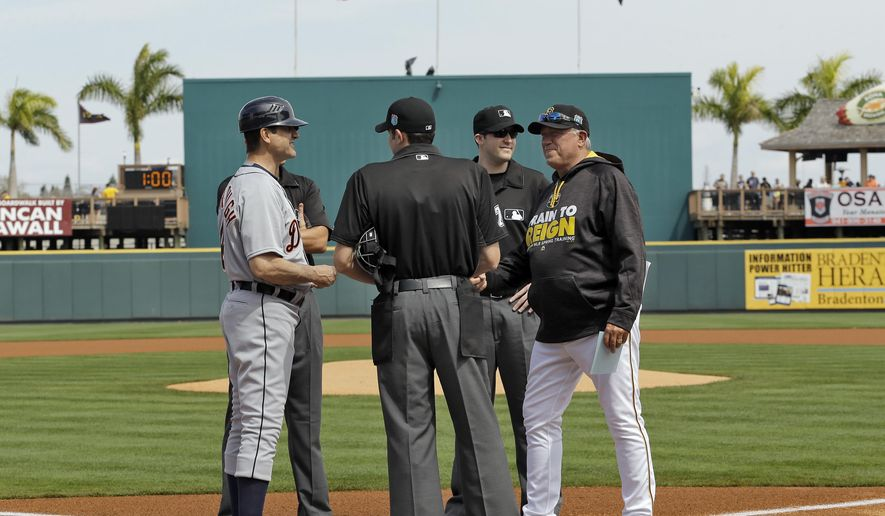 Michigan football coach Jim Harbaugh, left, chats with Pittsburgh Pirates manager Clint Hurdle, right, and the umpires after delivering the lineup card before a spring training baseball game between the Pirates and the Detroit Tigers Wednesday, March 2, 2016, in Bradenton, Fla. Harbaugh coach first base for the Tigers. (AP Photo/Chris O'Meara)
