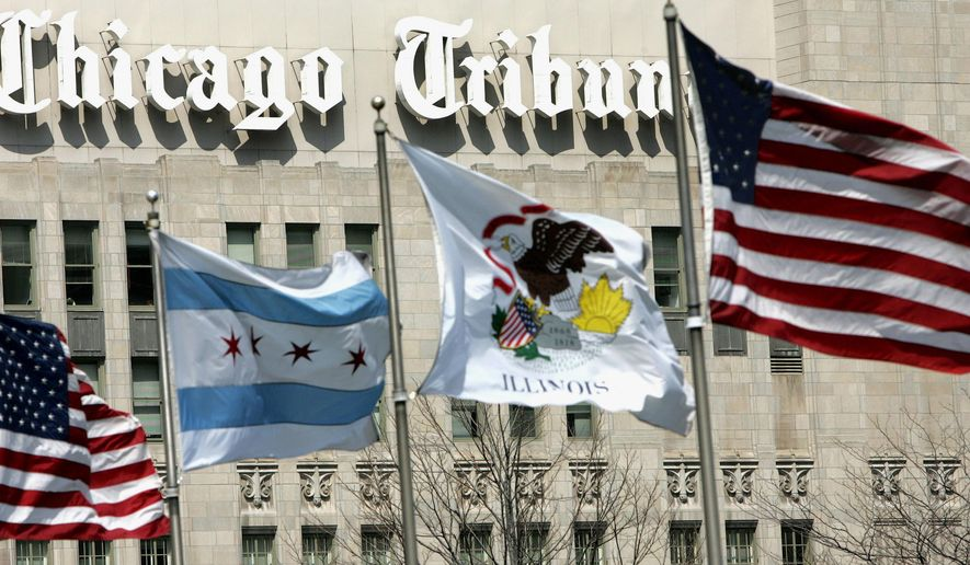 FILE - In this April 12, 2006, file photo, flags wave near the Chicago Tribune Tower in downtown Chicago. A week after naming a new CEO, Tribune Publishing Co. announced a reorganization, on Wednesday, March 2, 2016, naming each of its newspapers' editors as dual editors-in-chief and publishers. (AP Photo/Charles Rex Arbogast, File)