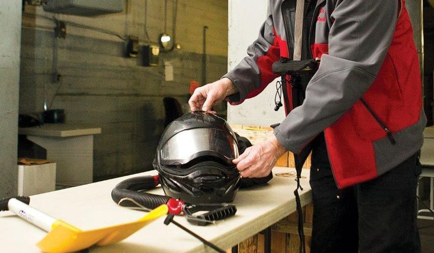 Bryan Shuster shows some of the gear he brings when snowmobiling as a safety precaution on Feb. 11, 2016 in Laramie, Wyo. The items include a bungee unit for stuck sleds, a helmet with a respirator, a transponder unit and a shovel that doubles as a probe for finding people buried in snow.(Jeremy Martin/Laramie Daily Boomerang via AP) MANDATORY CREDIT
