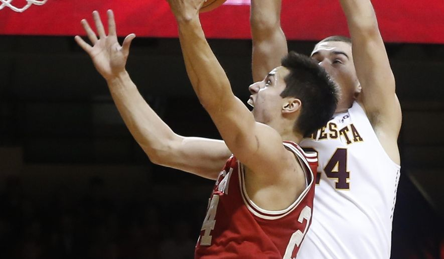 Wisconsin's Bronson Koenig, left, lays up as Minnesota's Joey King defends in the first half of an NCAA college basketball game Wednesday, March 2, 2016, in Minneapolis. (AP Photo/Jim Mone)