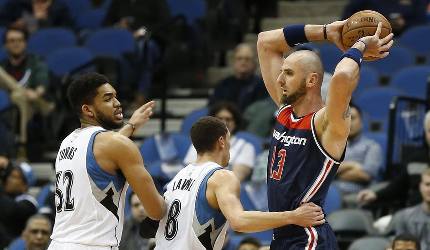 Washington Wizards center Marcin Gortat (13) protects the ball from Minnesota Timberwolves guard Zach LaVine (8) and forward Karl-Anthony Towns (32) in the first half of an NBA basketball game Wednesday, March 2, 2016 in Minneapolis. (AP Photo/Stacy Bengs)
