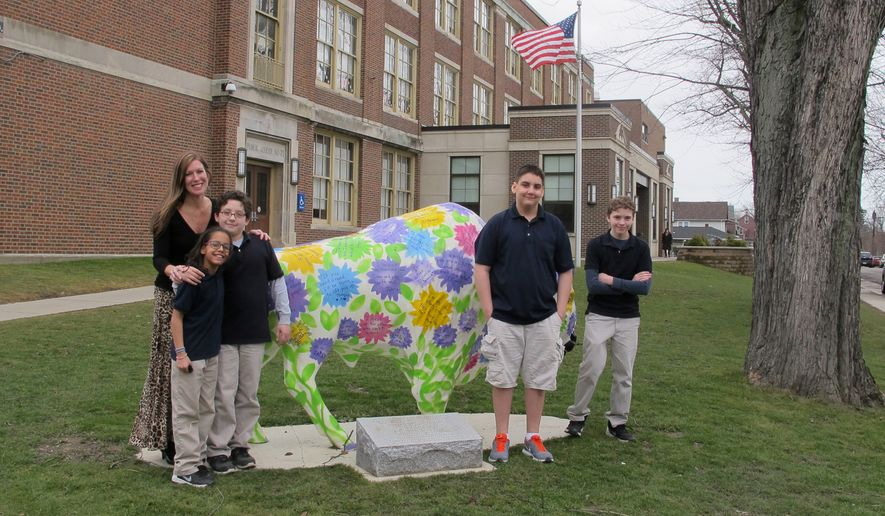 In this Feb. 29, 2016, file photo, teacher Kelly Gasior, left, and students, from left, Olivia Mashtaire, Ryan Lysek, Christian Vazquez and Tyler Lysek stand with a statue of a Buffalo that's been emblazoned with anti-bullying messages outside Lorraine Academy, Public School No. 72, in Buffalo, N.Y. (AP Photo/Carolyn Thompson)