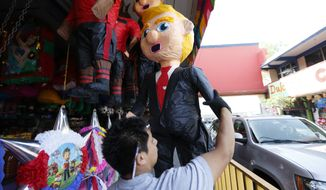 A vendor adjusts a pinata in the image of Republican presidential candidate Donald Trump Wednesday, March 2, 2016, in Tijuana, Mexico. Former Mexican President Vicente Fox on Wednesday stood by his comparison of Donald Trump to Adolf Hitler, saying the Republican presidential front-runner believes in the white supremacy. (AP Photo/Gregory Bull)