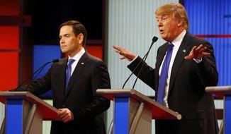 Donald Trump speaks as Sen. Marco Rubio listens during the Republican presidential debate Thursday night in Detroit. (Associated Press)