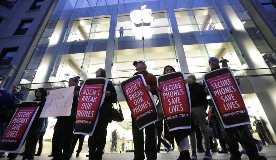 FILE - In this Tuesday, Feb. 23, 2016, file photo, protesters carry placards outside an Apple store in Boston. Tech companies, security experts and civil liberties groups are filing court briefs supporting Apple in its battle with the FBI. The groups oppose a judge's order that would require Apple to help federal agents hack an encrypted iPhone used by a San Bernardino mass shooter. (AP Photo/Steven Senne, File)