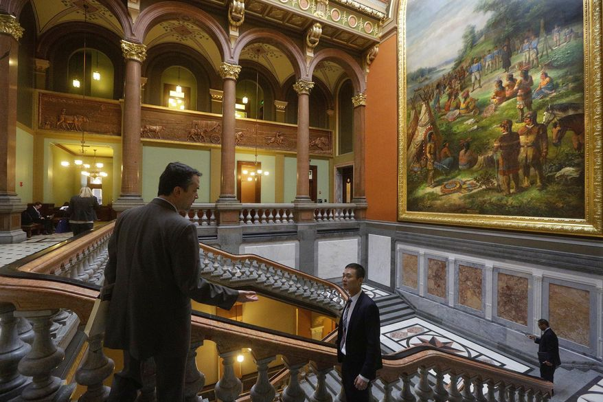 Lawmakers and lobbyist move through the hallways during session at the Illinois State Capitol Thursday, March 3, 2016, in Springfield, Ill. The Democrat-led Senate approved a measure that would allow an outside arbitrator to settle state-employee wages and working conditions in Illinois if union negotiations reach an impasse. (AP Photo/Seth Perlman)