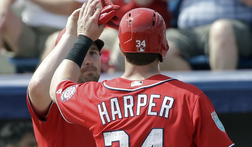 Washington Nationals' Daniel Murphy (20) gives Bryce Harper (34) a high five after Harper scored a run in the first inning against the New York Mets in a spring training baseball game, Thursday, March 3, 2016, in Viera, Fla. (AP Photo/John Raoux)