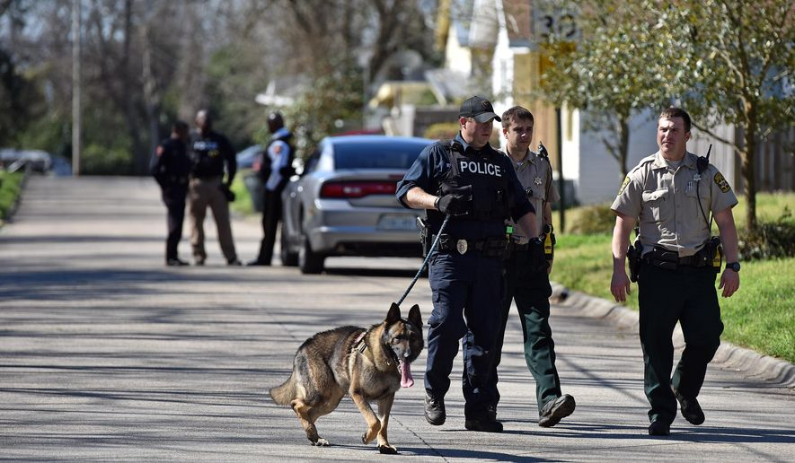 Vicksburg police and Warren County sheriff's deputies search Wednesday in a Vicksburg neighborhood, Miss., for escaped inmate Rafael McCloud, who is a suspect in a capital murder, on Wednesday, March 2, 2016. (Justin Sellers/The Clarion-Ledger via AP) MANDATORY CREDIT