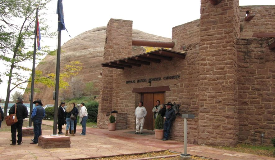 FILE - In this Oct. 21, 2010 photo, people gather outside the Navajo Nation Council chambers in Window Rock, Ariz. More than three-fourths of the 88-member Navajo Nation Council has been charged in an investigation into the use of discretionary funds. A long-running saga stemming from allegations that Navajo tribal officials schemed to give money to family members is drawing to a close. (AP Photo/Felicia Fonseca)