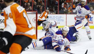 Edmonton Oilers' Cam Talbot, center, blocks a shot by Philadelphia Flyers' Sean Couturier, left, as Oilers' Lauri Korpikoski (28) and Darnell Nurse (25) also defend during the second period of an NHL hockey game, Thursday, March 3, 2016, in Philadelphia. (AP Photo/Matt Slocum)