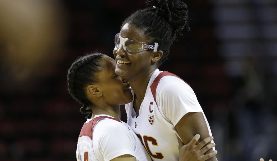 Southern California's Temi Fagbenle, right, is embraced by Sadie Edwards in the final moments in an NCAA college basketball game against Washington State in the Pac-12 women's tournament, Thursday, March 3, 2016, in Seattle. USC won 77-73. (AP Photo/Elaine Thompson)