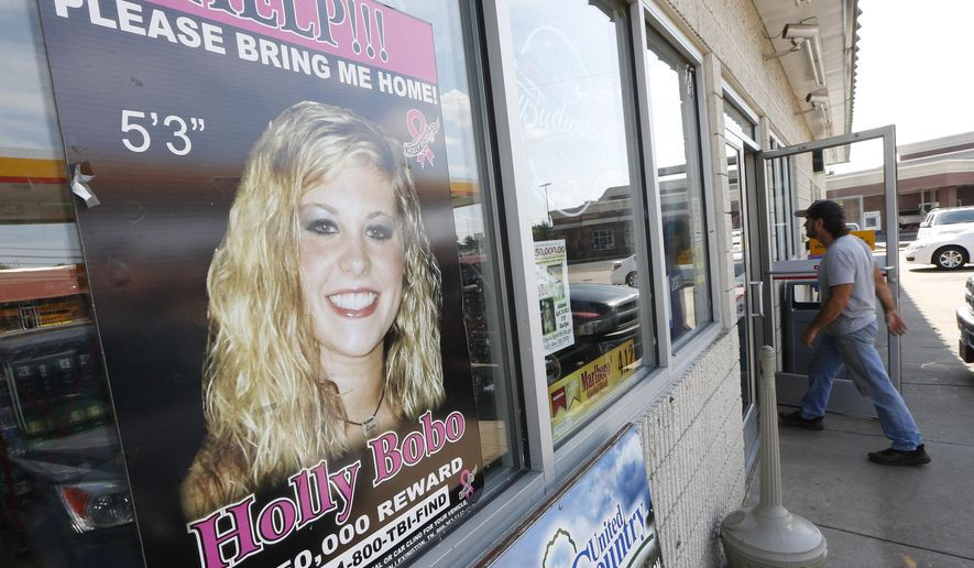 FILE - In this Sept. 9, 2014 file photo, a poster offering a reward for information in the disappearance of Holly Bobo, is displayed in a store window in Parsons, Tenn.  A Tennessee judge has set a target trial date in early 2017 for at least one of three men charged with murder in the 2011 disappearance of Bobo.  (AP Photo/Mark Humphrey, File)