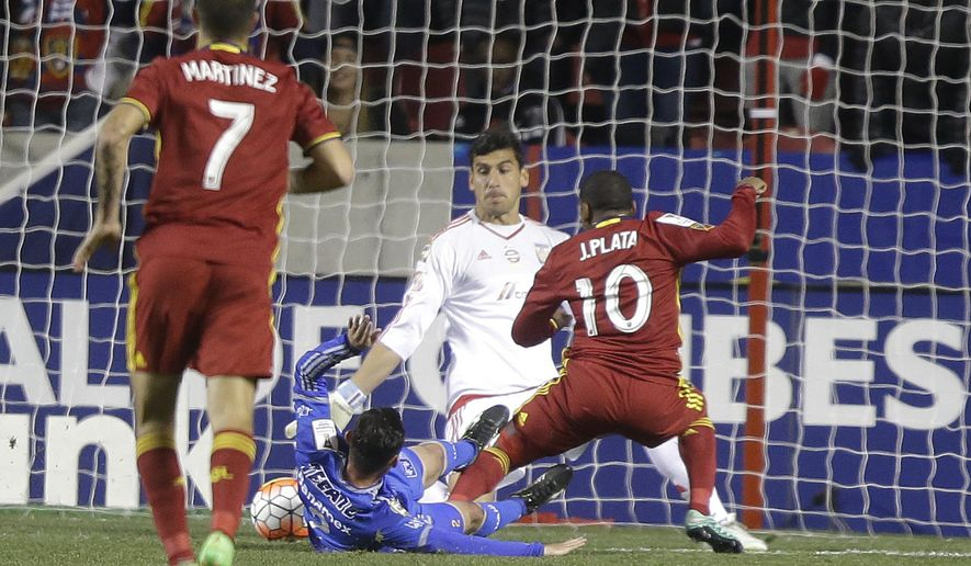 Real Salt Lake's Joao Plata (10) scores against Tigres goalkeeper Nahuel Guzman (1) as Israel Jimenez, on ground, defends during the first half in the second leg of a CONCACAF Champions League soccer quarterfinal Wednesday, March 2, 2016, at Rio Tinto Stadium, in Sandy, Utah. (AP Photo/Rick Bowmer)