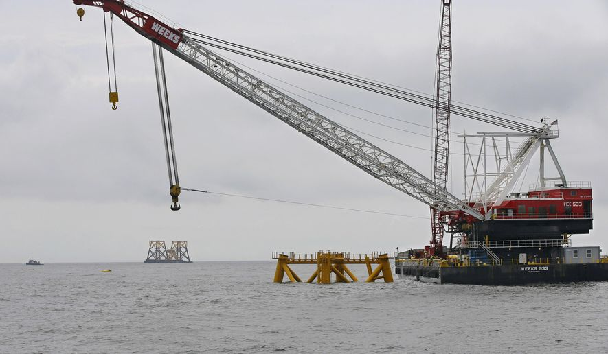 FILE - In this July 27, 2015, file photo, the first foundation jacket installed by Deepwater Wind in the nation's first offshore wind farm construction project is seen next to a floating construction crane on the waters of the Atlantic Ocean off Block Island, R.I. Business leaders and politicians who gathered for an industry conference in Boston during early March 2016, pointed to deep-pocketed investors and major European offshore wind companies that are increasingly committing to projects all along the East Coast as evidence that a domestic industry dreamed about for nearly two decades has finally come. (AP Photo/Stephan Savoia, File)