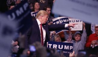 Republican presidential candidate Donald Trump points out a protester during a rally at Macomb Community College, Friday, March 4, 2016, in Warren, Mich. (AP Photo/Carlos Osorio)