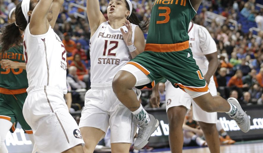 Miami's Jessica Thomas (3) drives against Florida State's Brittany Brown (12) and Ivey Slaughter (23)  during the first half of an NCAA college basketball game in the Atlantic Coast Conference tournament in Greensboro, N.C., Friday, March 4, 2016. (AP Photo/Chuck Burton)