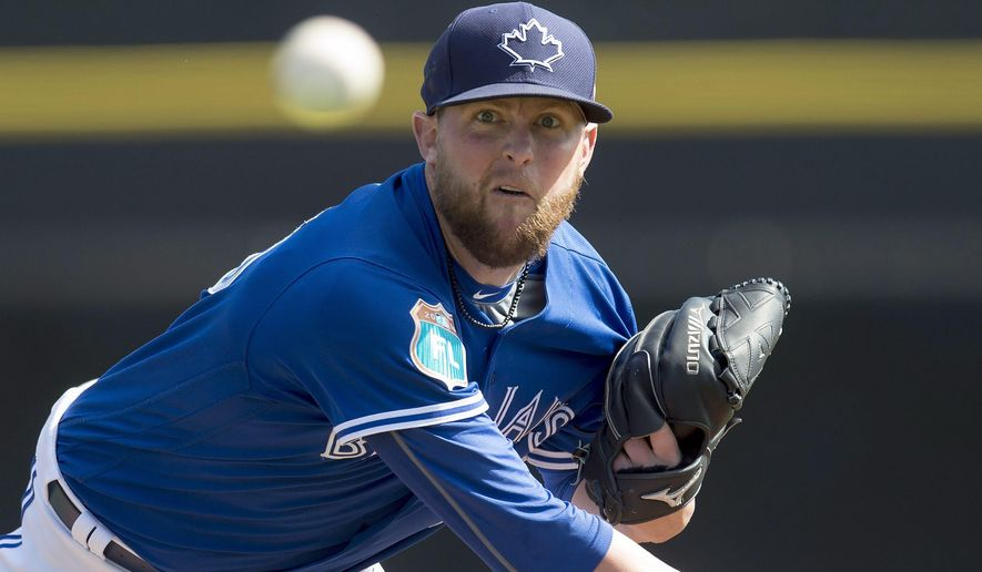 Toronto Blue Jays pitcher Drew Storen throws warmup pitches before facing the Baltimore Orioles in the fifth inning of a spring training baseball game in Dunedin, Fla., Friday, March 4, 2016. (Frank Gunn/The Canadian Press via AP) MANDATORY CREDIT