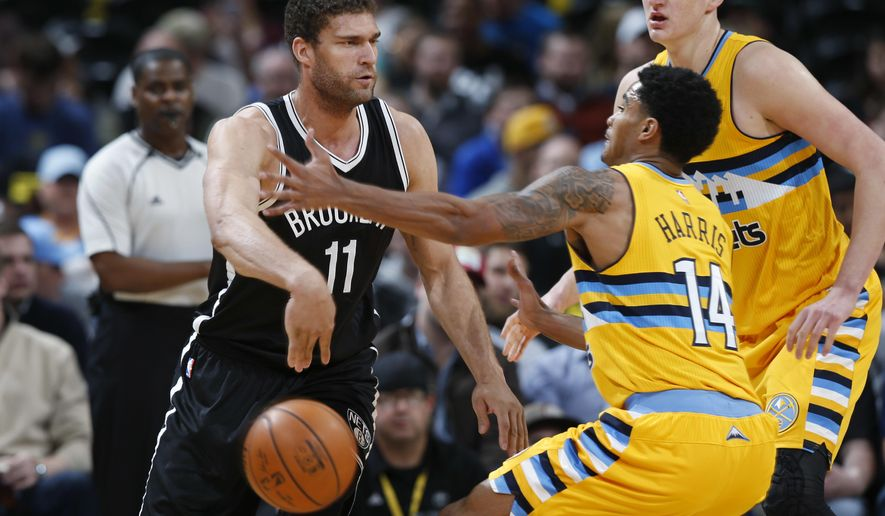 Brooklyn Nets center Brook Lopez, left, passes the ball under the arm of Denver Nuggets guard Gary Harris as Nikola Jokic, back right, helps defend during the first half of an NBA basketball game Friday, March 4, 2016, in Denver. (AP Photo/David Zalubowski)