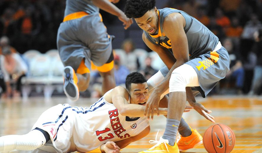 Mississippi forward Anthony Perez (13) and Tennessee guard Shembari Phillips tangle for a loose ball during the first half of an NCAA college basketball game, Saturday, March 5, 2016, in Knoxville, Tenn. (Adam Lau/Knoxville News Sentinel via AP) MANDATORY CREDIT