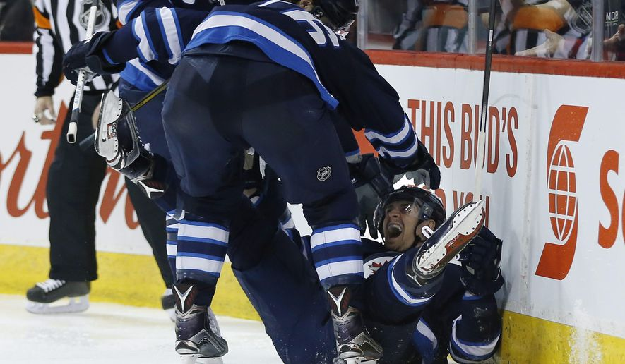 Winnipeg Jets' Drew Stafford (12), Blake Wheeler (26), and Mark Scheifele (55) celebrate Scheifele's goal against the Montreal Canadiens during the second period of an NHL hockey game, Saturday, March 5, 2016 in Winnipeg, Manitoba. (John Woods/The Canadian Press via AP) MANDATORY CREDIT