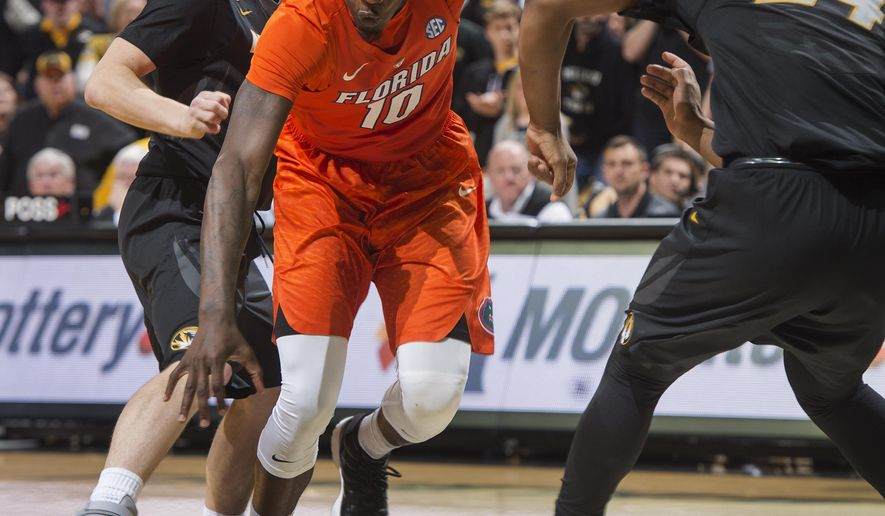 Florida's Dorian Finney-Smith, center, drives between Missouri's Kevin Puryear, right, and Jimmy Barton during the second half of an NCAA college basketball game Saturday, March 5, 2016, in Columbia, Mo. Florida won the game 82-72. (AP Photo/L.G. Patterson)