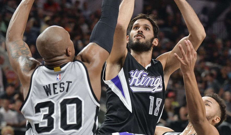 Sacramento Kings forward Omri Casspi (18), of Israel, shoots against San Antonio Spurs forwards David West (30) and Kyle Anderson during the first half of an NBA basketball game, Saturday, March 5, 2016, in San Antonio. (AP Photo/Darren Abate)