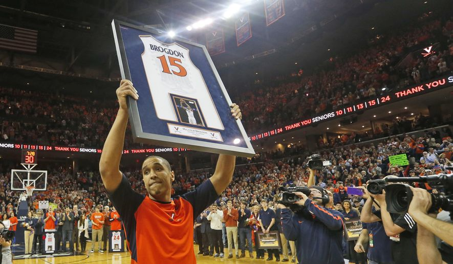 Virginia guard Malcolm Brogdon (15) holds a commemorative jersey as he is introduced prior to the team's NCAA college basketball game against Louisville in Charlottesville, Va., Saturday, March 5, 2016. Brogdon is a graduating senior. (AP Photo/Steve Helber)