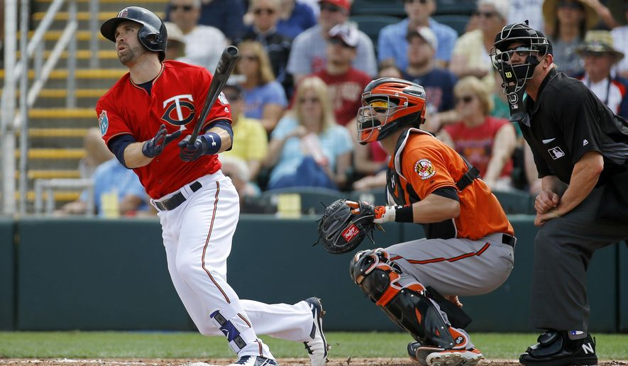 Minnesota Twins' Brian Dozier, left, watches his solo home run in front of Baltimore Orioles catcher Caleb Joseph (36) and home plate umpire Jeff Kellogg in the first inning of a spring training baseball game in Fort Myers, Fla., Saturday, March 5, 2016. (AP Photo/Patrick Semansky)