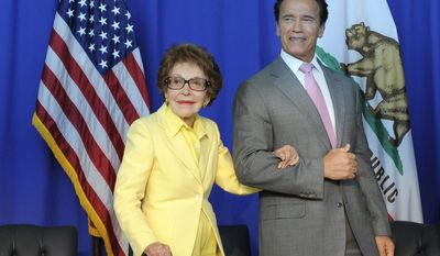 Nancy Reagan, left, is escorted by California Governor Arnold Schwarzenegger after the ceremonial signing of California Senate Bill 944 and Assembly Bill 1911 honoring President Ronald Reagan for his life's accomplishments and contributions to California on Wednesday, July 28, 2010, at the Ronald Reagan Presidential Library in Simi Valley, Calif. (AP Photo/Adam Lau)