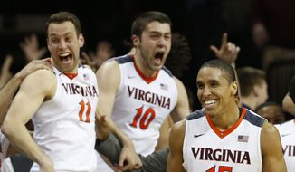 Virginia's Malcolm Brogdon (15), Evan Nolte (11) and Mike Tobey (10) celebrate during the second half of an NCAA college basketball game against Louisville in Charlottesville, Va., Saturday, March 5, 2016. Virginia won 68-46. (AP Photo/Steve Helber)