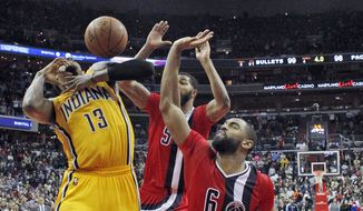 Indiana Pacers forward Paul George (13) reacts after he was fouled by Washington Wizards guard Alan Anderson (6) with forward Markieff Morris, behind, during the second half of an NBA basketball game Saturday, March 5, 2016, in Washington. George made both free throws to give the Pacers the win100-99. (AP Photo/Alex Brandon)