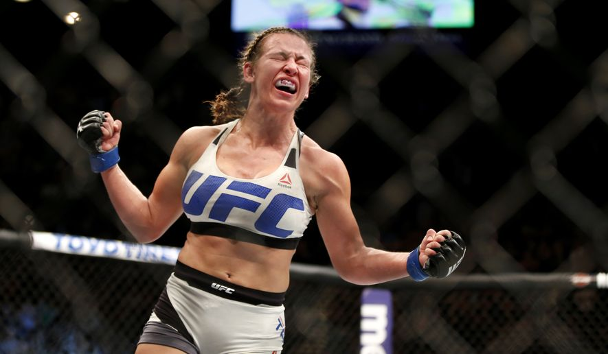 Miesha Tate celebrates victory over Holly Holm in their UFC 196 women's bantamweight mixed martial arts match Saturday, March 5, 2016, in Las Vegas. (AP Photo/Eric Jamison)